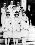 Des femmes en uniformes blancs posent dans des marches.
