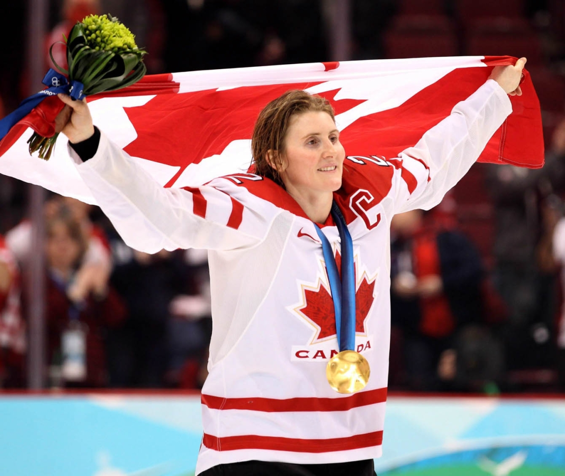 Hayley Wickenheiser, médaille au cou, porte le drapeau canadien