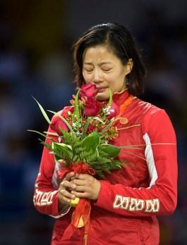 Une athlète tient des fleurs sur un podium