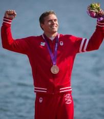 Un athlète célèbre sa médaille les poings dans les airs