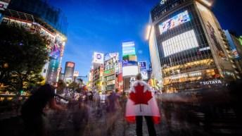 Une personne pose avec le drapeau canadien au centre-ville de Tokyo