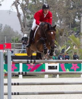 Un cavalier d'Équipe Canada et sa monture sautent par dessus un obstacle à Lima 2019