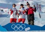 Trois athlètes sur le podium devant une piste de big air