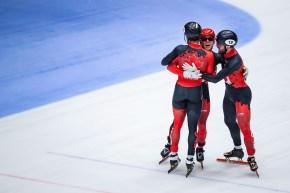 Trois patineurs canadiens se serrent dans leurs bras