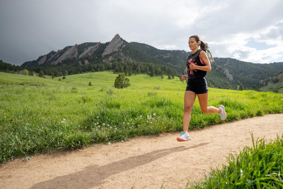 Lanni Marchant court dans un paysage verdoyant.
