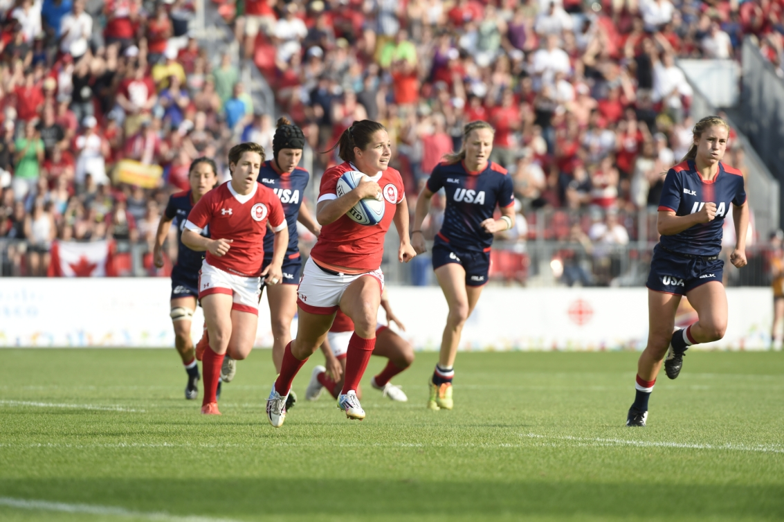 Canadian player runs with ball during rugby match