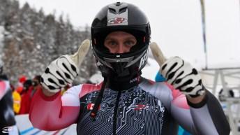 Un athlète de bobsleigh fait les signes du pouce vers le haut après sa descente.