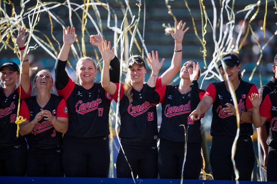 Des joueuses de softball posent pour la caméra sous des confettis.