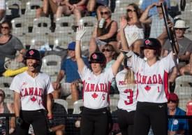 Trois joueuses de softball lèvent les bras en célébration