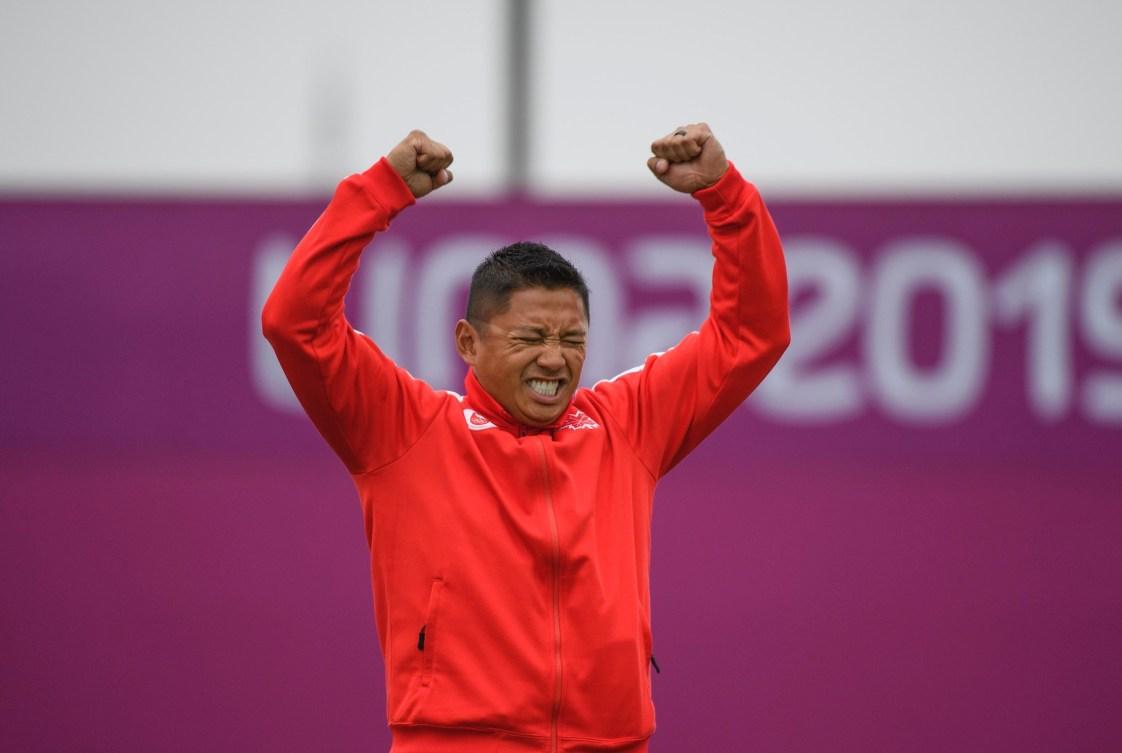 Un athlète lève les bras en signe de victoire