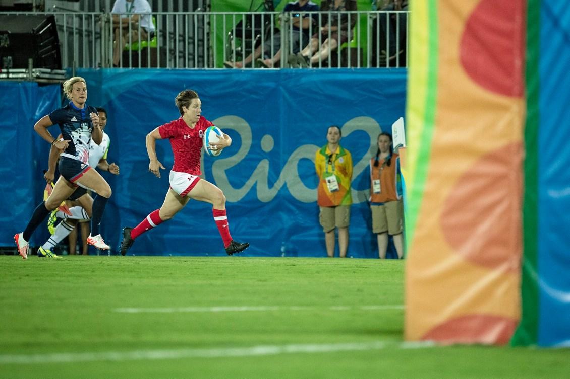 Une joueuse de rugby court avec le ballon
