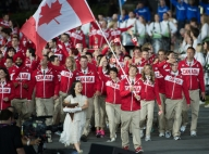 Two-time triathlon medallist Simon Whitfield bears the flag for team Canada during the opening ceremonies to the 2012 London Olympics, on July 27, 2012. THE CANADIAN PRESS/HO, COC - Jason Ransom