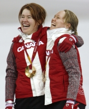Clara Hughes and Cindy Klassen sing O Canada together after winning gold and bronze in the 5000m at Turin 2006.