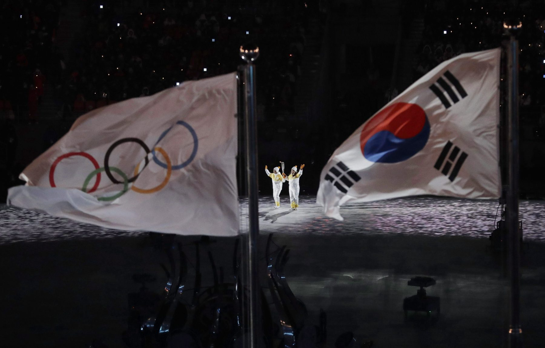 The Olympic torch is carried into the stadium during the opening ceremony of the 2018 Olympic Winter Games