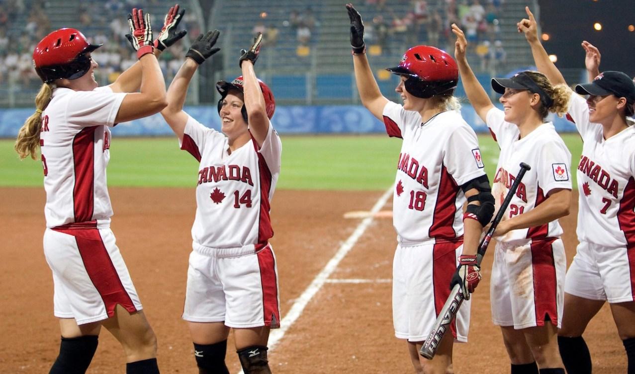 Canadian softball players celebrate a run scoring
