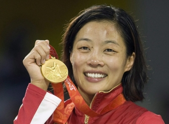 Canada's Carol Huynh from Hazelton, B.C. holds up her gold medal for the women's freestyle 48kg wrestling during victory ceremonies at the Beijing 2008 Summer Olympics in Beijing, Saturday, August 16, 2008.
