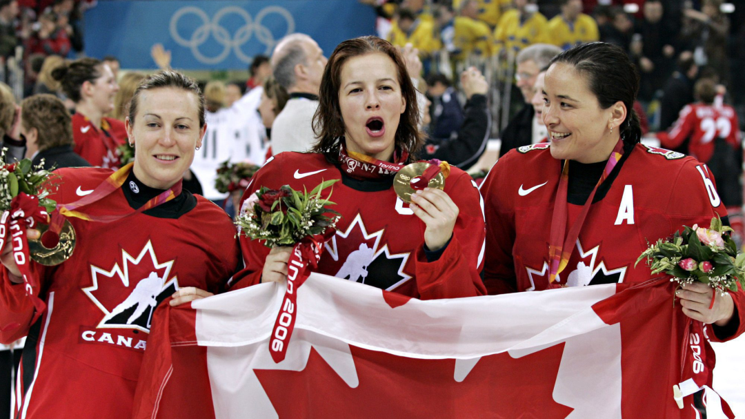 Campbell holds the Canadian flag and her medal with two teammates