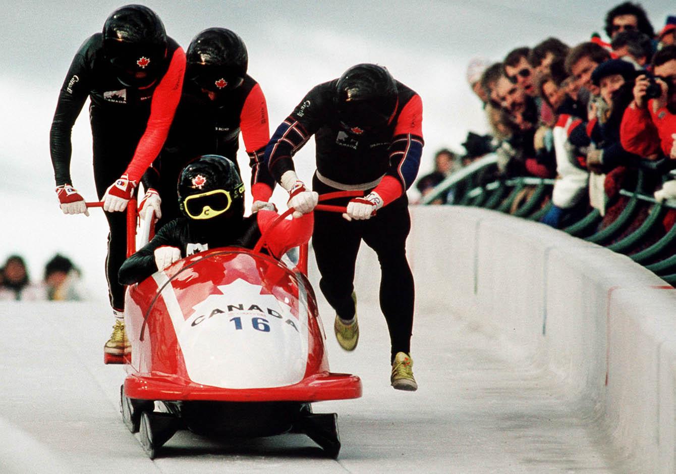Four men running with bobsleigh