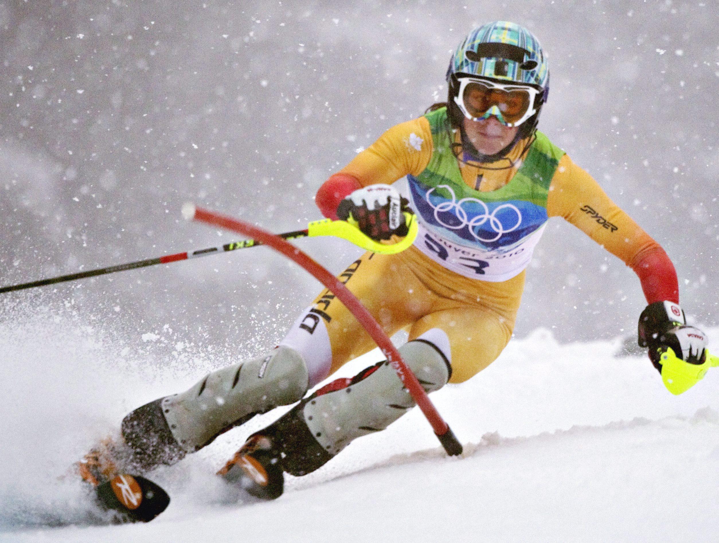 An alpine skier goes around a slalom gate