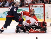 USA's Meghan Duggan and Canada's goaltender Shannon Szabados keep their eyes on the puck during second period women's gold medal Olympic hockey action at the 2010 Winter Olympic Games in Vancouver, Thursday, Feb. 25, 2010. THE CANADIAN PRESS/Jonathan Hayward