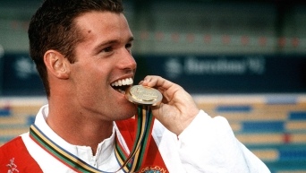 Mark Tewksbury bites his medal during the medal ceremony