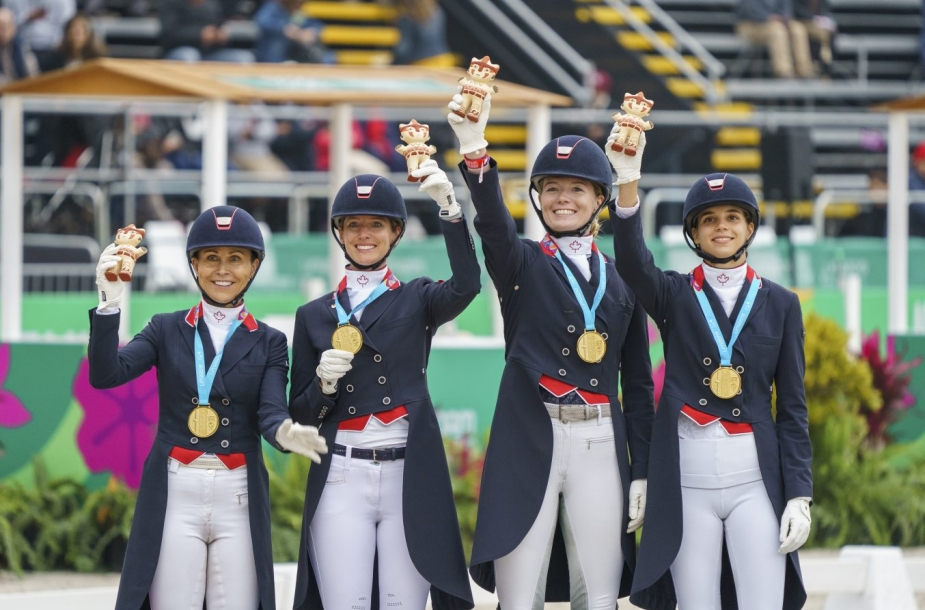 Four equestrian athletes holding up figurines