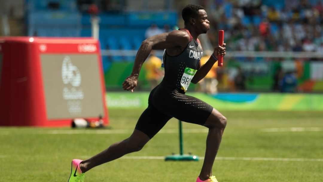 Aarom Brown runs with a relay baton