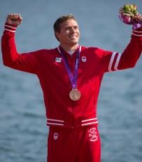 Mark de Jonge raises arms in celebration while wearing his medal