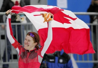 Hughes holding Canadian flag and smiling