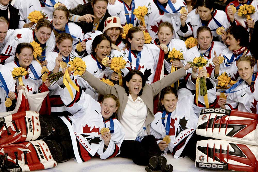 Team Canada women post on ice after winning gold