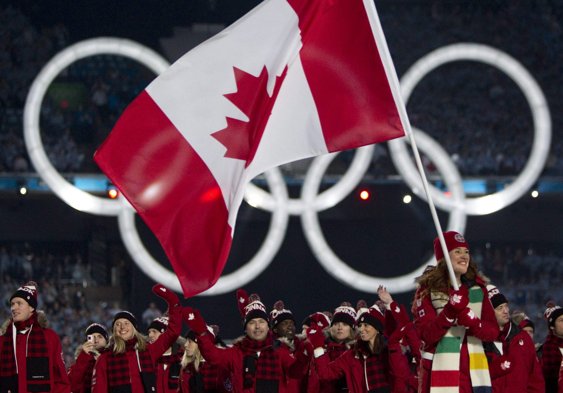 Canadian Olympic speed skater and cyclist Clara Hughes leads the Canadian team during the athlete's parade at the opening ceremony