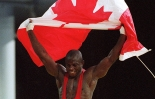 Canada's Daniel Igali waves the Canadian flag after winning the gold medal in wrestling at the 2000 Sydney Olympic Games. (CP Photo/ COC)