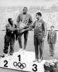 Harry Jerome shakes hands with other medallists on podium