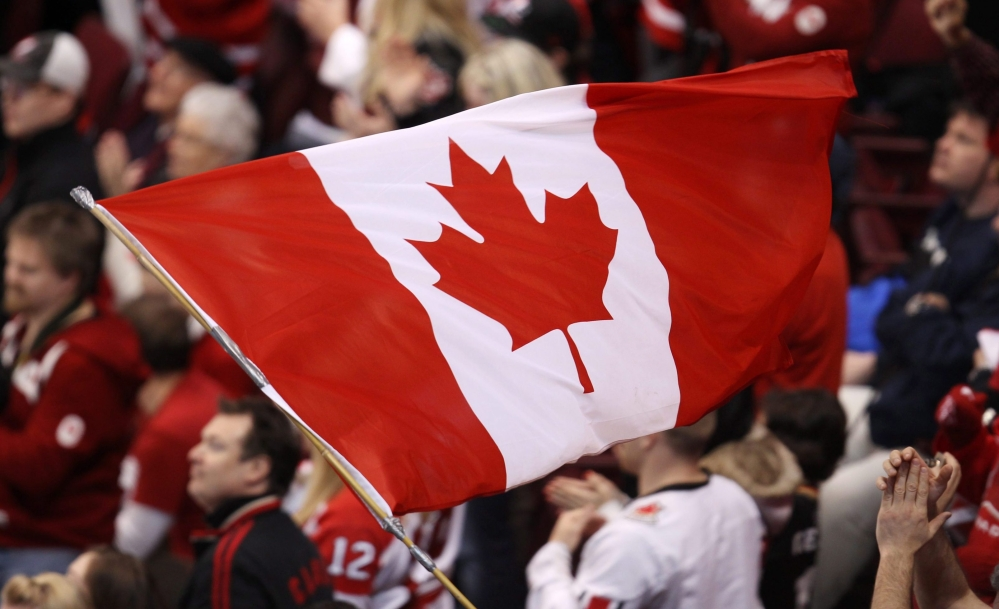A Canadian flag waved by someone in the crowd.