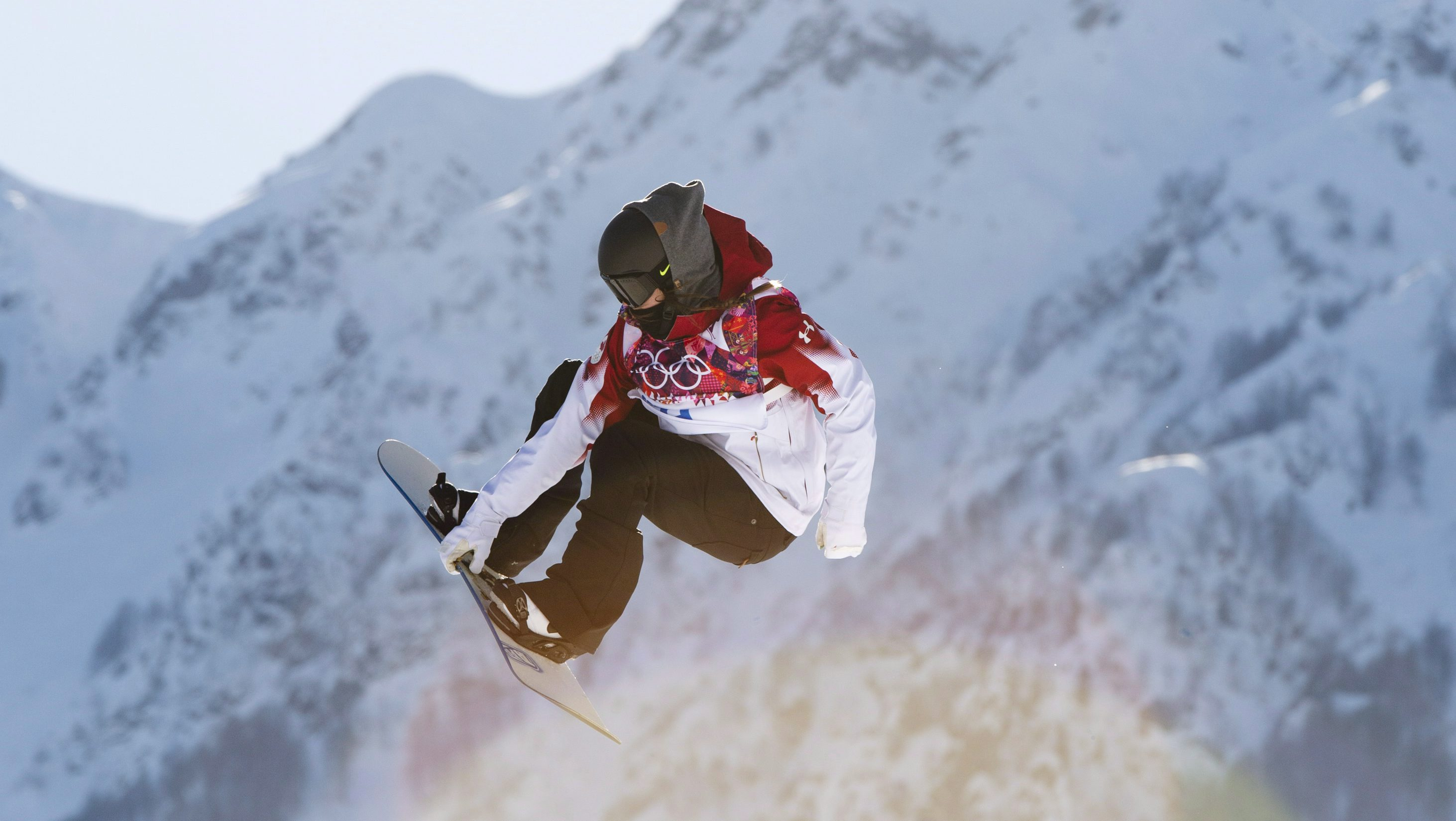 Snowboarder, Spencer O'Brien in the air with mountains in the background.