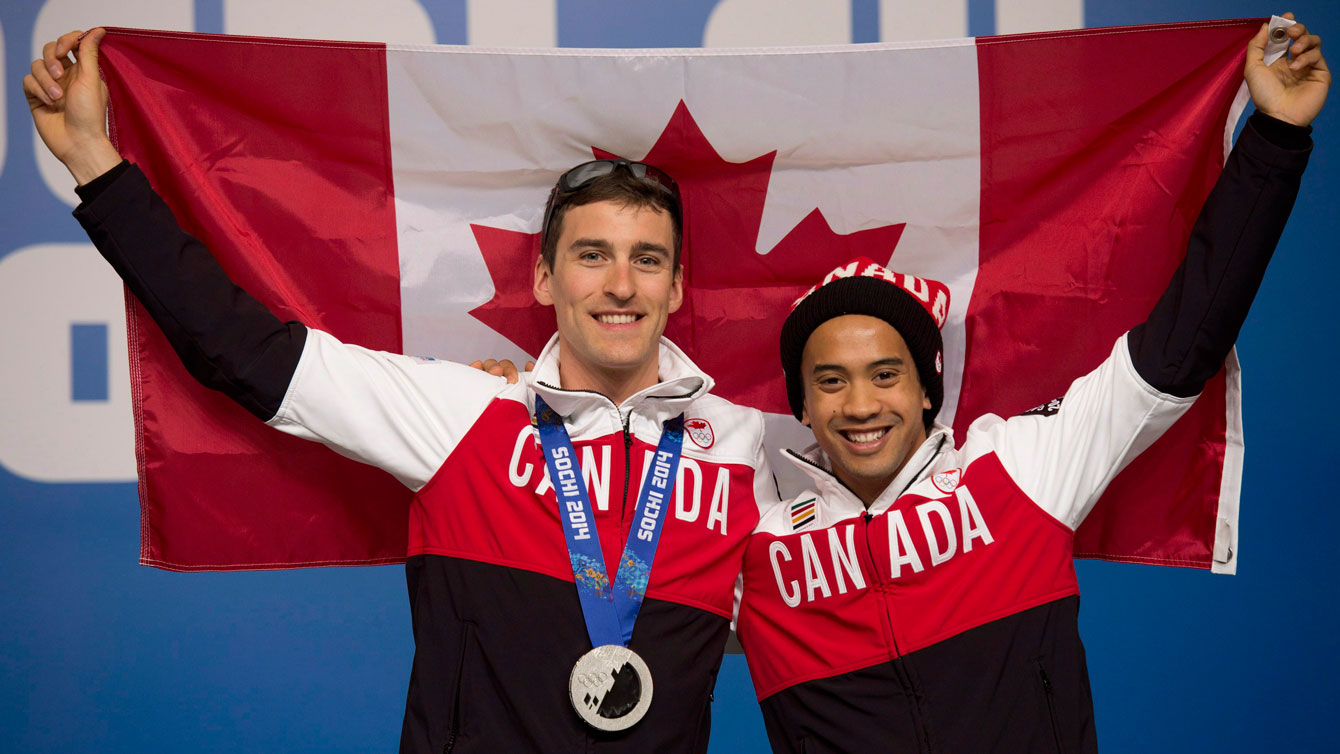 Canadian speed skaters Denny Morrison and Gilmore Junio hold up a Canadian flag following a news conference at the Sochi Winter Olympics Sunday February 16, 2014 in Sochi, Russia. THE CANADIAN PRESS/Adrian Wyld