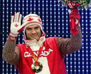 Canada's Duff Gibson celebrates his gold medal during the medal ceremony for the Men's Skeleton competition at the Turin 2006 Olympic Winter Games in Turin, Italy, Saturday Feb 18, 2006. (AP Photo/Greg Baker)