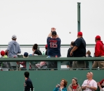 Fans sitting on the Green Monster watch a home run leave the park. Photo: CP