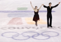 Canada's Tessa Virtue and Scott Moir salute the crowd following their compulsory dance in the ice dance competition Friday February 19, 2010 at the 2010 Vancouver Olympic Winter Games in Vancouver. THE CANADIAN PRESS/Paul Chiasson