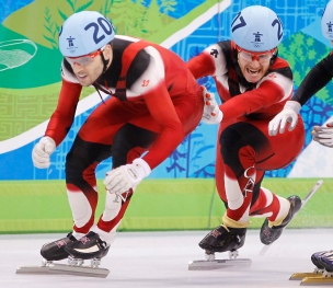 Canada's Olivier Jean, right, pushes teammate Francois-Louis Tremblay to go on to win the gold medal in the men's 5000 metre relay final in the short track speedskating competition Friday February 26, 2010 at the 2010 Vancouver Olympic Winter Games in Vancouver. THE CANADIAN PRESS/Paul Chiasson