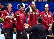 Canada's Charles Hamelin receives his medal as teammates Guillaume Bastille, Francois Hamelin, Olivier Jean and Francois-Louis Tremblay, left to right, look on after winning the gold medal in the men's 5000 metre relay in the short track speedskating competition Friday February 26, 2010 at the Olympic Winter Games in Vancouver. THE CANADIAN PRESS/Paul Chiasson