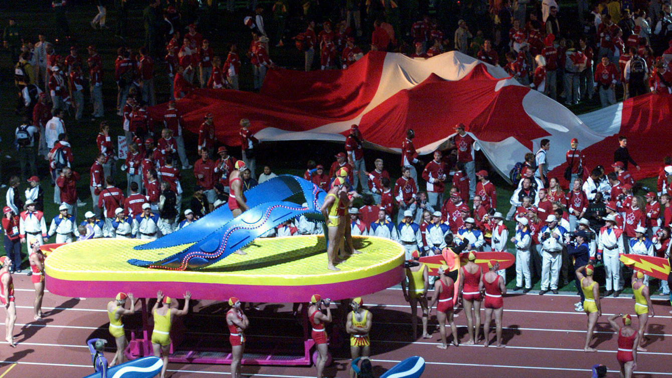 Canadian athletes begin to unfurl the giant flag at Sydney 2000 Closing Ceremony. The 18m x 9m flag rivals several Ceremony floats.