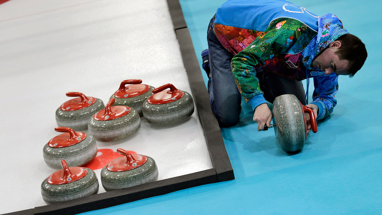 An ice crew worker makes adjustments to curling rocks at Sochi 2014.