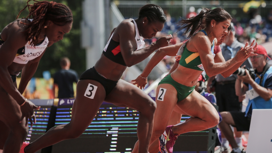 Khamica Bingham (centre) takes off at the start of the women's 100m Pan Am Games heats in Toronto