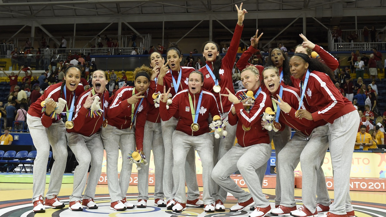 Basketball team poses with their gold medals