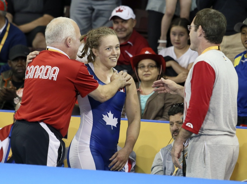 Dorothy Yeat (blue) of Montreal celebrates her gold medal with her coaches in the freestyle wrestling finals at the PanAmerican Games in Mississauga, Ont., Friday, July 17, 2015. Photo by Mike Ridewood/COC