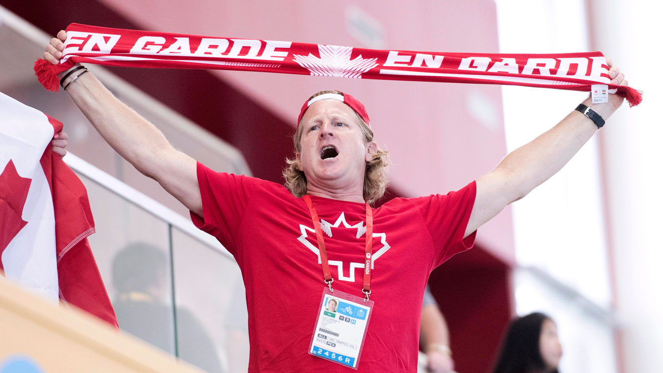 Curt Harnett holding a Team Canada scarf above his head