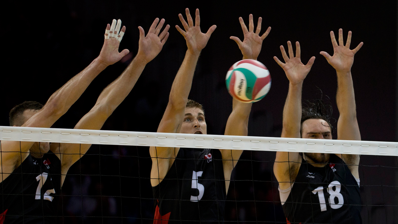 Canada's Rudy Verhoeff, center, jumps to block along with teammates Gavin Schmitt, left, and Nicholas Hoag in their men's volleyball preliminary against Mexico at TO2015
