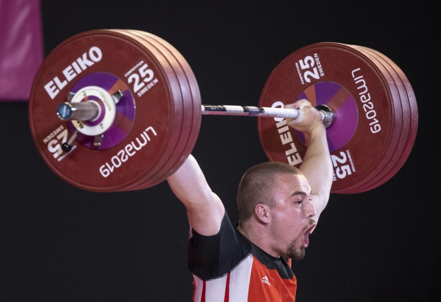 Boady Santavy screams as he lifts weights over head