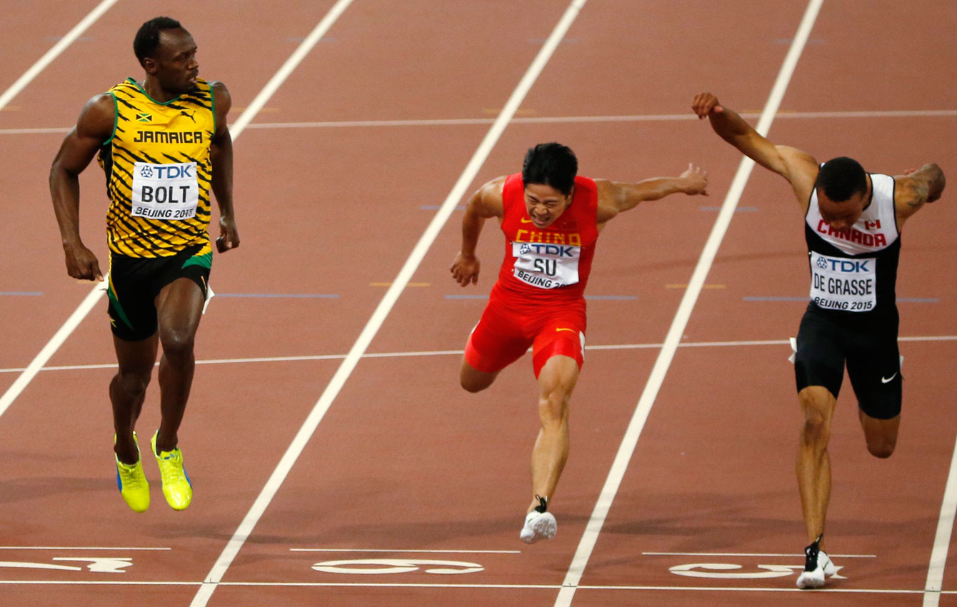 Jamaica's Usain Bolt looks over his left shoulder as Bingtian Su (China) and Andre De Grasse of Canada finish in the semifinals of the men's 100m in Beijing, China on August 23, 2015. All three men advanced to the World Championship final, with De Grasse and Bolt sharing a time of 9.96s.